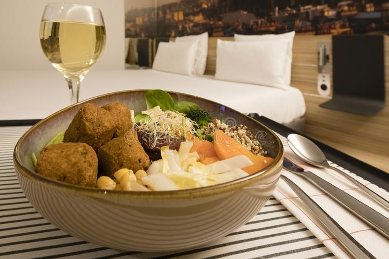 Hotel Room service: vegan meal and white wine with the bed in the backgroud.  stock photos