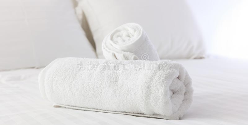 Hotel`s bedroom. White fluffy, rolled towels, linen sheets and pillows on a bed. Close up view. Hotel`s bedroom. White fluffy, rolled towels, linen sheets and stock photos
