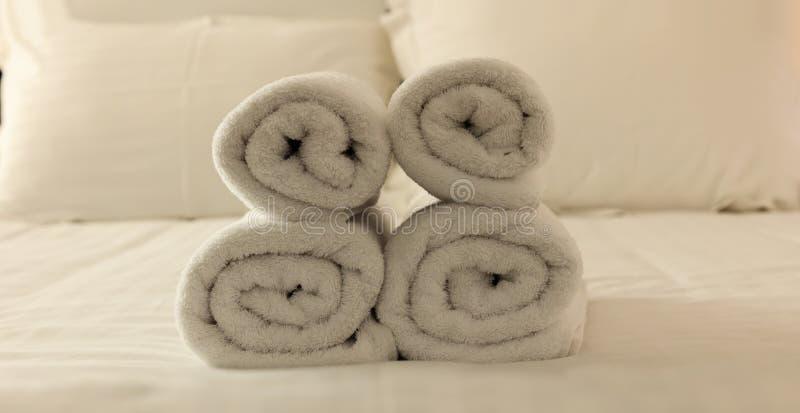 Hotel` s slaapkamer Witte pluizige, gerolde handdoeken, linnenbladen en hoofdkussens op een bed Sluit omhoog mening stock afbeelding
