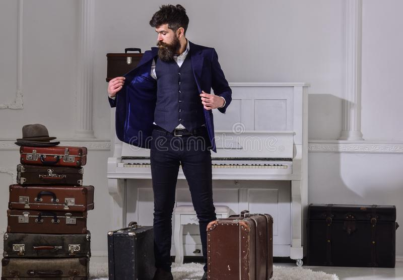 Hotel service concept. Man, traveller with beard and mustache with luggage, luxury white interior background. Macho. Elegant on strict face stands near pile of stock photos