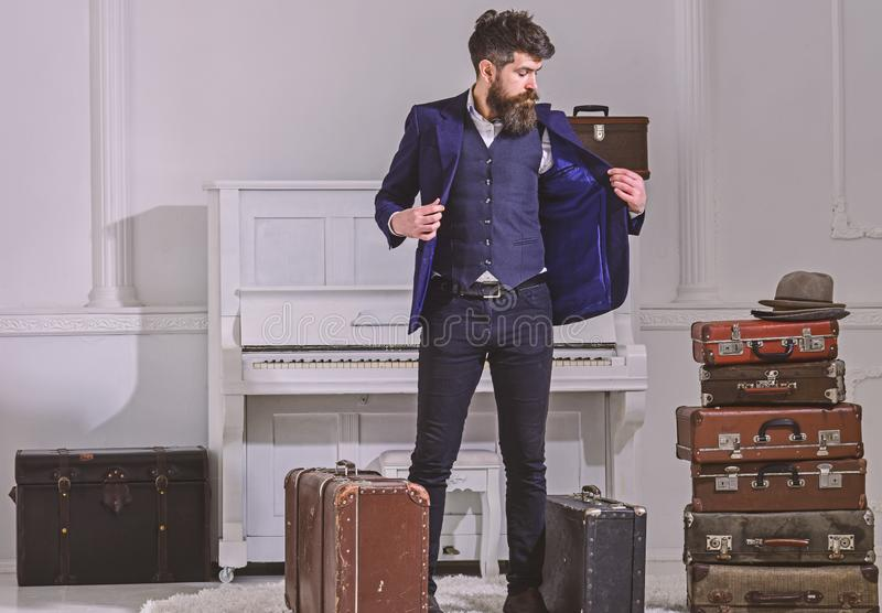 Hotel service concept. Man, traveller with beard and mustache with luggage, luxury white interior background. Macho. Elegant on strict face stands near pile of royalty free stock photos