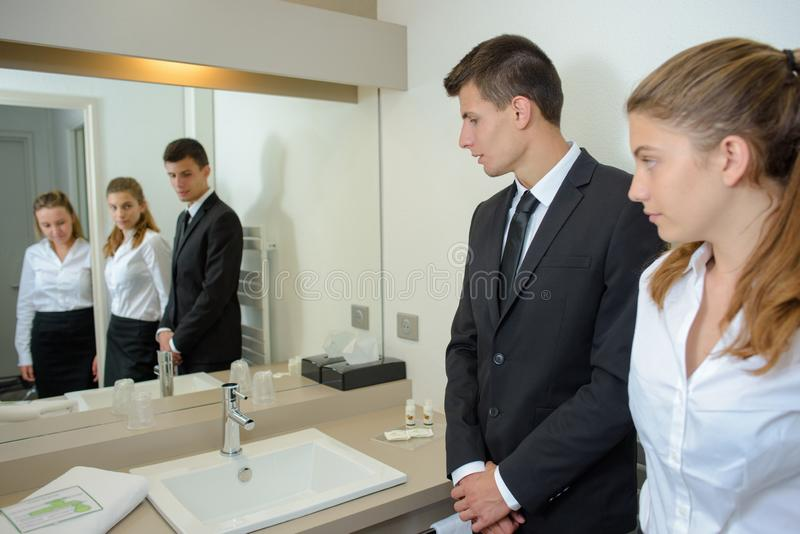Hotel staff reflected in bathroom mirror. Hotel royalty free stock photo