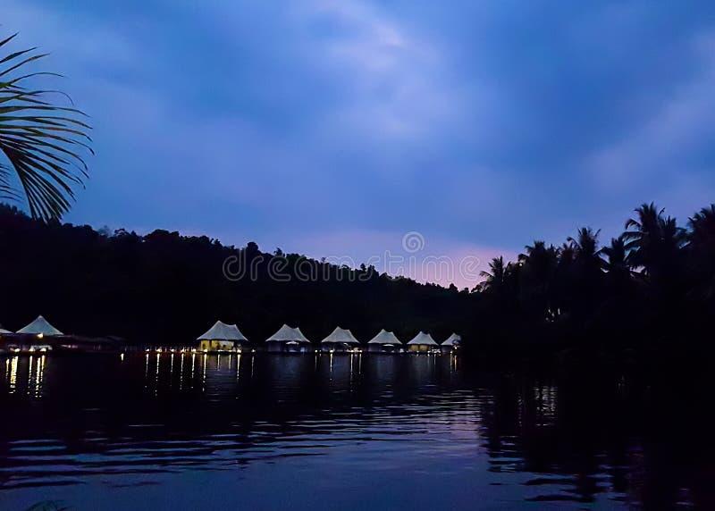 hotel tented di ecoturismo della giungla di 4 fiumi che entra in vista intorno ad una curvatura nel fiume di Kong alla penombra immagine stock