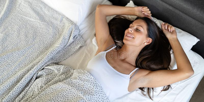 Hotel, travel and happiness concept. Beautiful woman sleeping in bed. Beautiful woman sleeping in bed. Hotel, travel and happiness concept royalty free stock photography