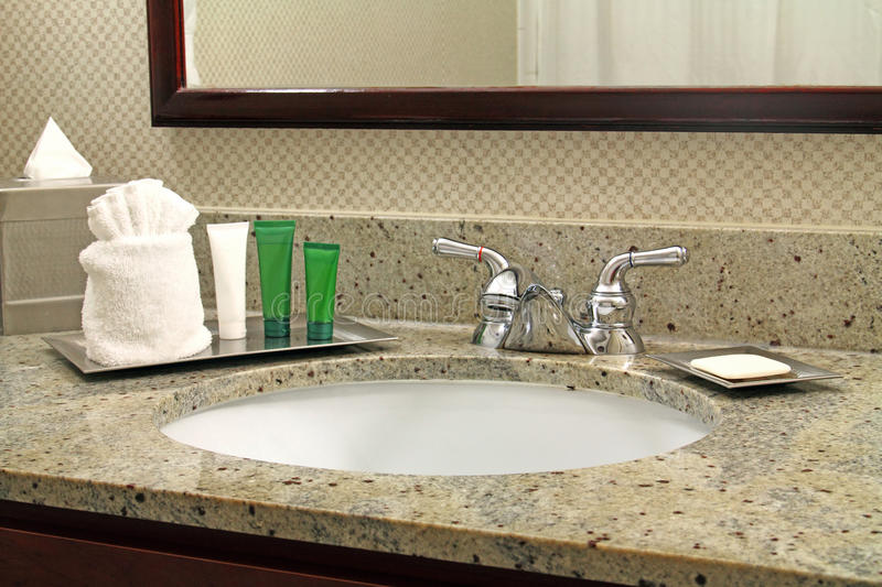 Hotel Vanity and Toiletries. Vanity with chrome finish faucet and granite counter top in hotel bathroom. Toiletries, tubes and bottles are in silver trains and royalty free stock images