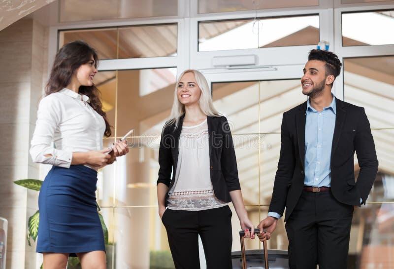 Hotel-Verwalter Welcome Business Couple in der Lobby, Wirtschaftler-Gruppen-Mann und Frauen-Gäste kommen an lizenzfreie stockbilder