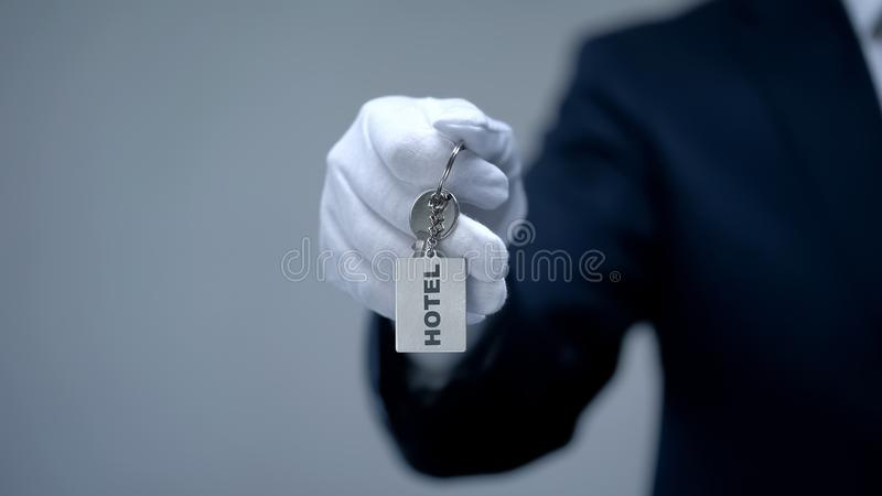 Hotel word on keychain in receptionist hand, room reservation, luxury services. Stock photo stock photo