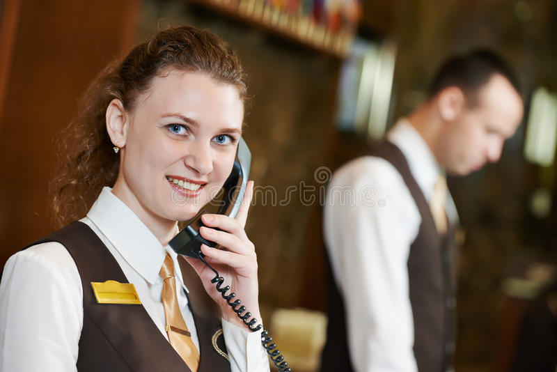 Hotel worker with phone on reception. Happy female receptionist worker with phone standing at hotel counter royalty free stock image