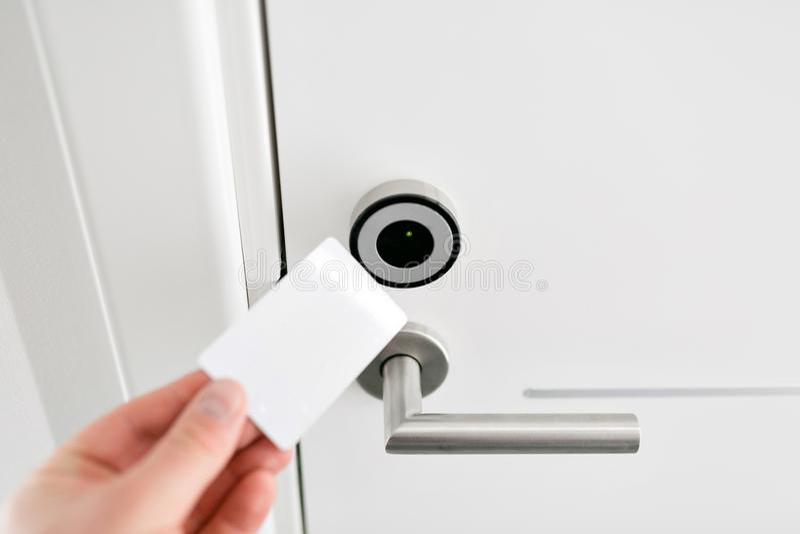 Hoteldeur - Jonge mens die een keycard voor de elektronische sensor van een ruimtedeur houden Conceptenreis of zaken royalty-vrije stock afbeeldingen