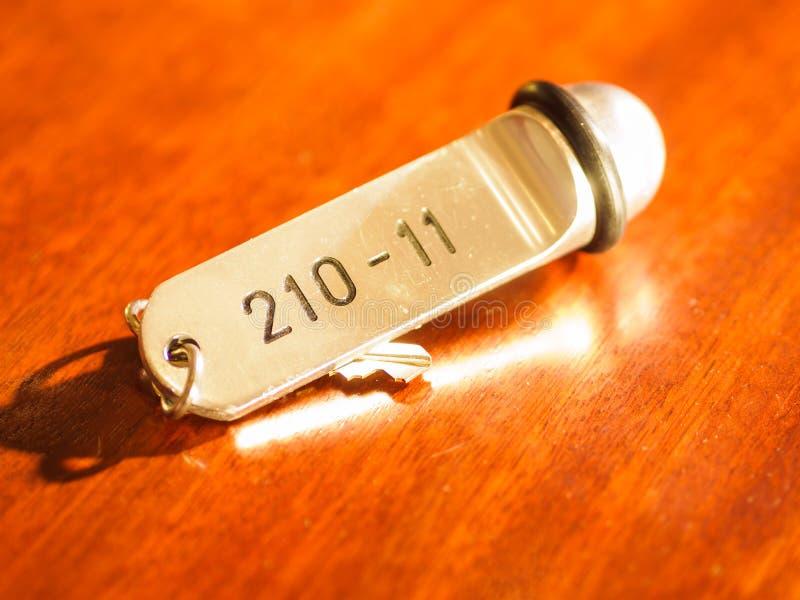 Hotelklok en sleutel die op het bureau liggen royalty-vrije stock foto's