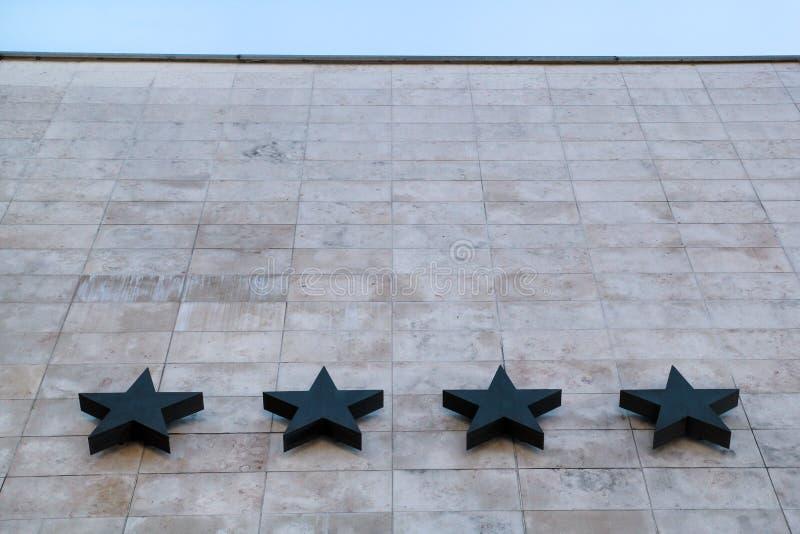 Hotell och gästfrihet/fyra stjärnor på stenväggen av hotellet/kvaliteten av hotell- och motellservice arkivbild