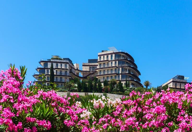 Hotellbyggnad bland blommor och grönska mot blå himmel fotografering för bildbyråer