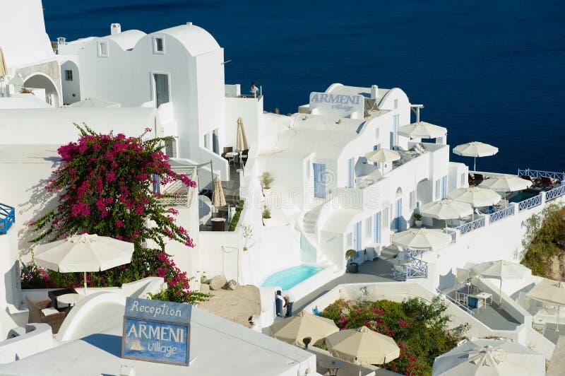Hotellbyggnader på klippan med en havssikt till den vulkaniska calderaen i Oia, Grekland royaltyfria bilder