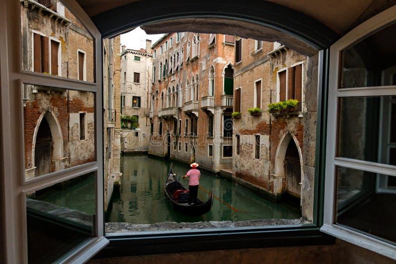 Hotellfönstersikt av den Venedig kanaler, byggnader och gondoljären arkivfoton