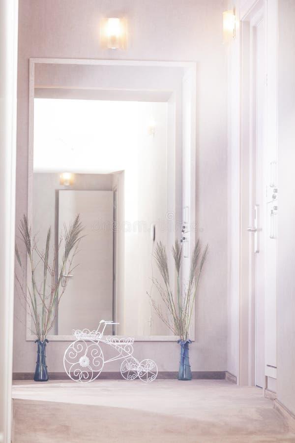 Hotellkorridorinre, dekorativ cykel, blommor och en stor spegel arkivfoton