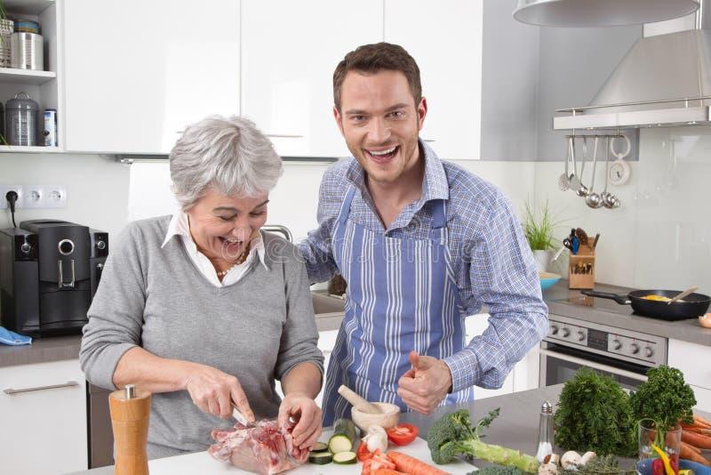Hotellmamma: ung man och äldre kvinna som tillsammans lagar mat griskött royaltyfri foto