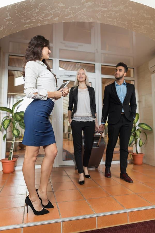 Hotellreceptionisten Meeting Business Couple i lobby, Businesspeoplegruppmannen och kvinnagäster ankommer royaltyfri fotografi