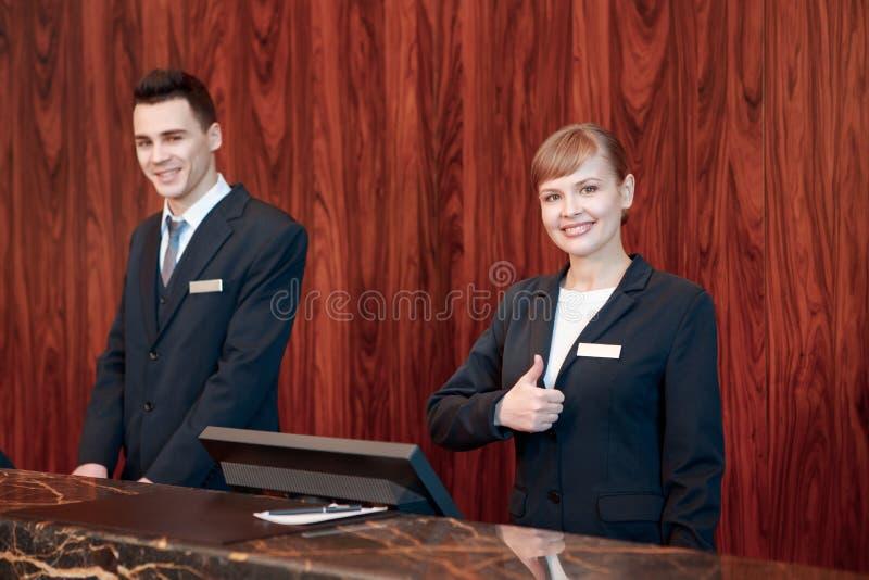Hotellreceptionister bak räknaren royaltyfria foton