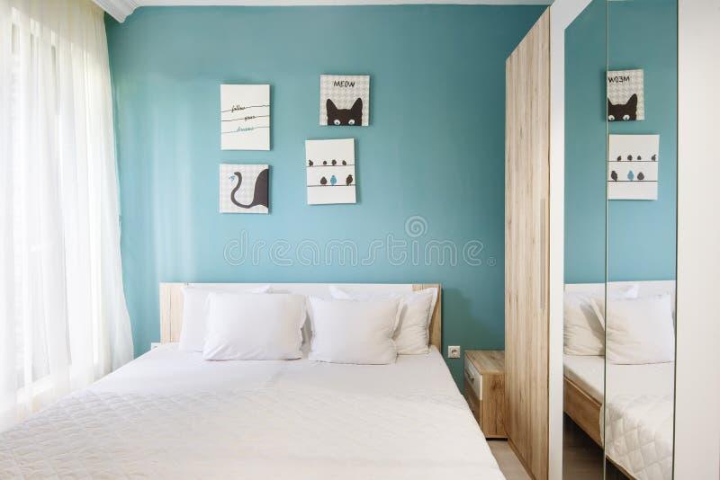 Hotellsovrum med blåa väggar, vita gardiner, örngott och ark arkivbild