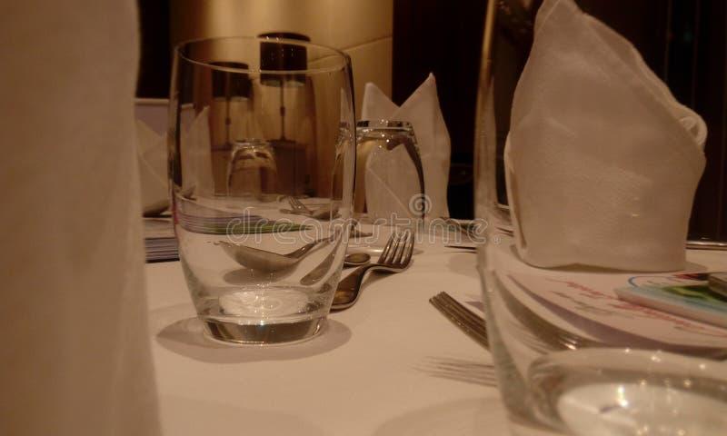 Hotelltabell som täckas med exponeringsglas av vatten, matplattan, gaffeln och skeden i rent för ett kommande parti royaltyfri fotografi