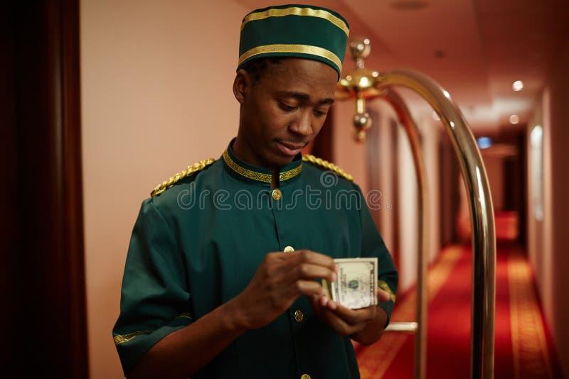 Hotelowa Bellboy liczenia gotówka obrazy royalty free