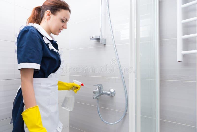 Hotelowa gospodyni czyści łazienkę zdjęcia royalty free