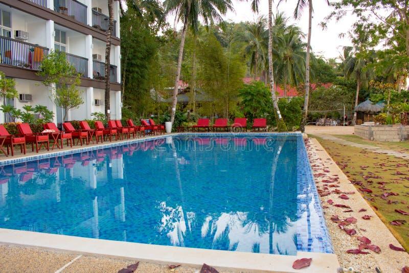 Hotelowy DoubleGem, El Nido, Filipiny - 26/02/2019: basen z czerwonymi krzesłami zdjęcia royalty free