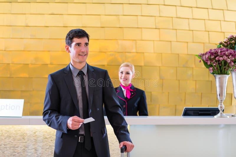 Hotelowy recepcjonista sprawdza wewnątrz mężczyzna daje kluczowej karcie zdjęcia royalty free