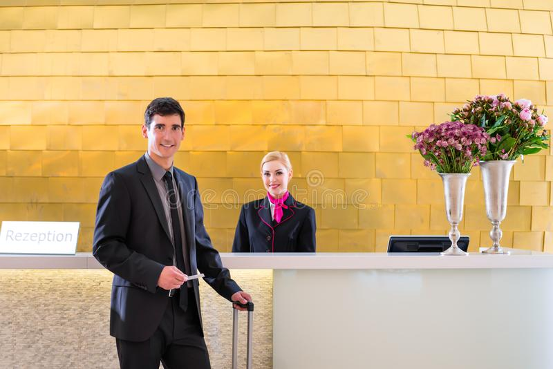 Hotelowy recepcjonista sprawdza wewnątrz mężczyzna daje kluczowej karcie zdjęcia stock