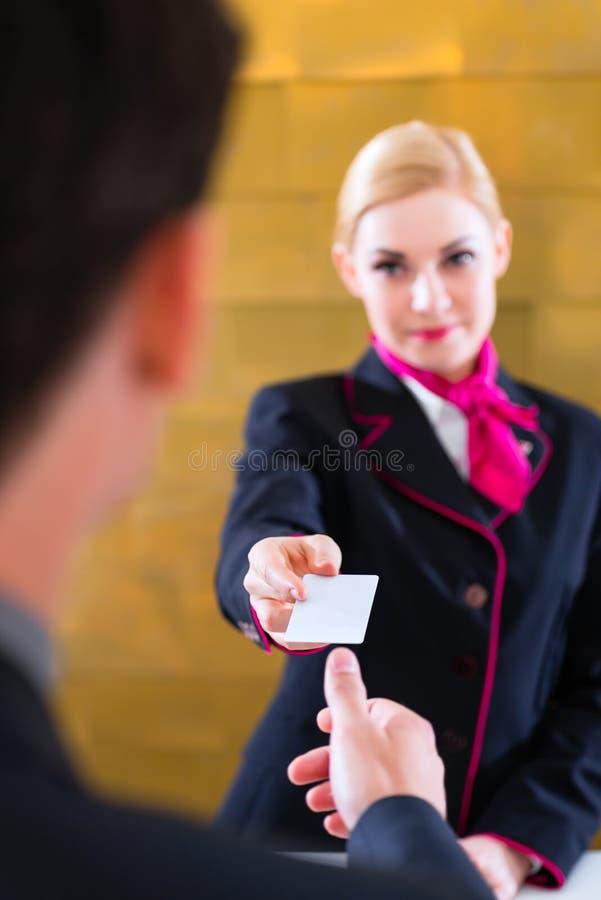 Hotelowy recepcjonista sprawdza wewnątrz mężczyzna daje kluczowej karcie obraz royalty free