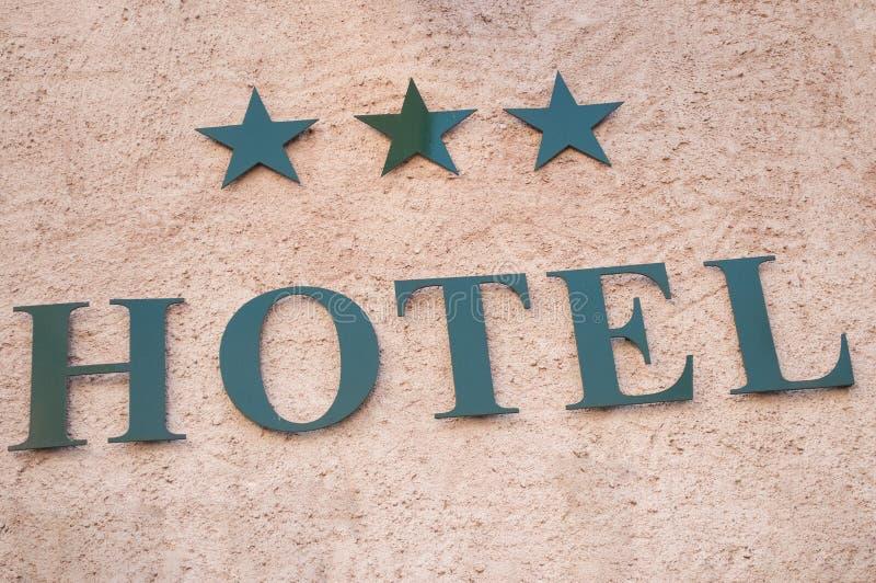 Hotelowy signage z trzy gwiazdami na drylującej ścianie obraz stock