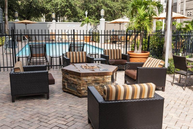 Hotelpatio mit dem Pool, Feuergrube und Möbeln zum sich zu entspannen stockbild