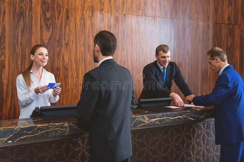 Hotelpersonal, das ihre Gäste registriert stockfotografie