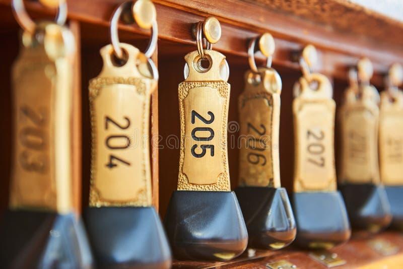 Hotelschlüssel mit Zimmernummer hängend an der Aufnahme lizenzfreie stockbilder