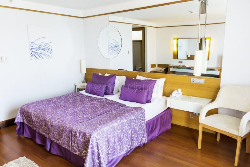 Hotelschlafzimmer im Purpur mit klassischem Bett lizenzfreie stockfotografie