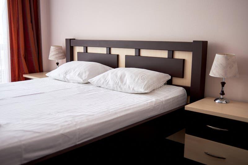 Hotelschlafzimmerinnenraum mit hölzernem Doppelbett mit weißem Blatt, weichen Kissen und Nachttisch, Kopienraum stockfotografie