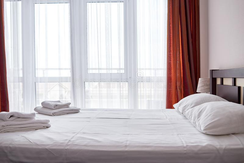 Hotelschlafzimmerinnenraum mit leerem Doppelbett mit hölzerner Kopfende und großem Fenster, Kopienraum Weißes Blatt, weiche Kisse lizenzfreies stockbild