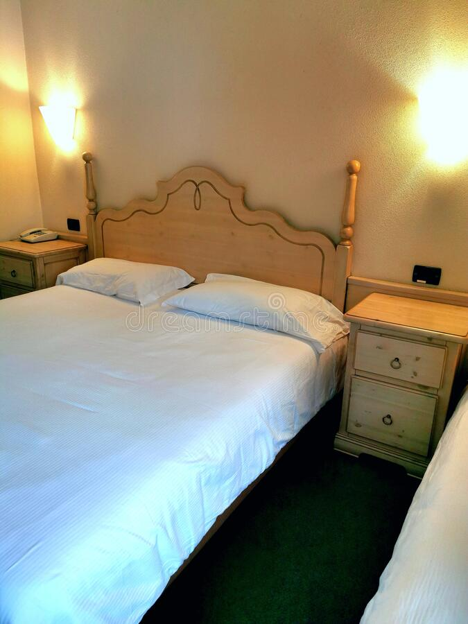 Hotelslaapkamer met bedtafels en telefoon stock foto