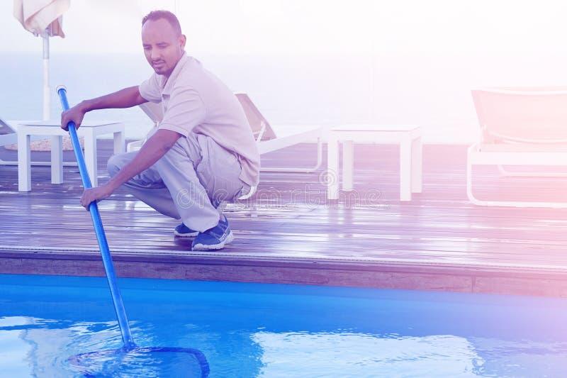 Hotelu pięcioliniowy pracownik czyści basenu utrzymanie zdjęcie royalty free