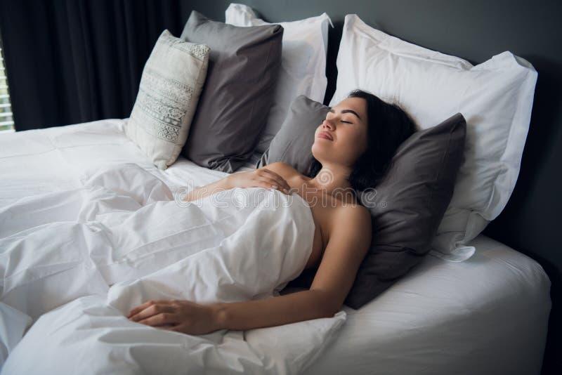 Hotelu, podróży i szczęścia pojęcie, - piękny kobiety dosypianie w łóżku zdjęcie stock