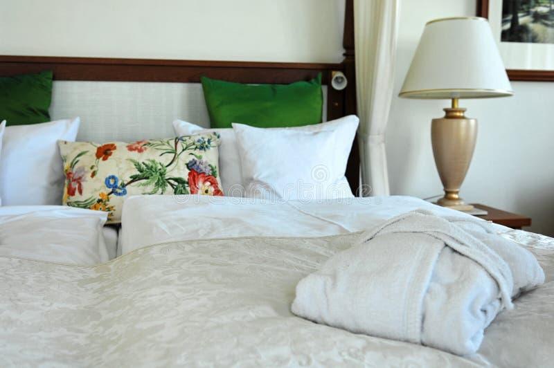 Hotelzimmer/Bademantel auf Bett lizenzfreie stockbilder