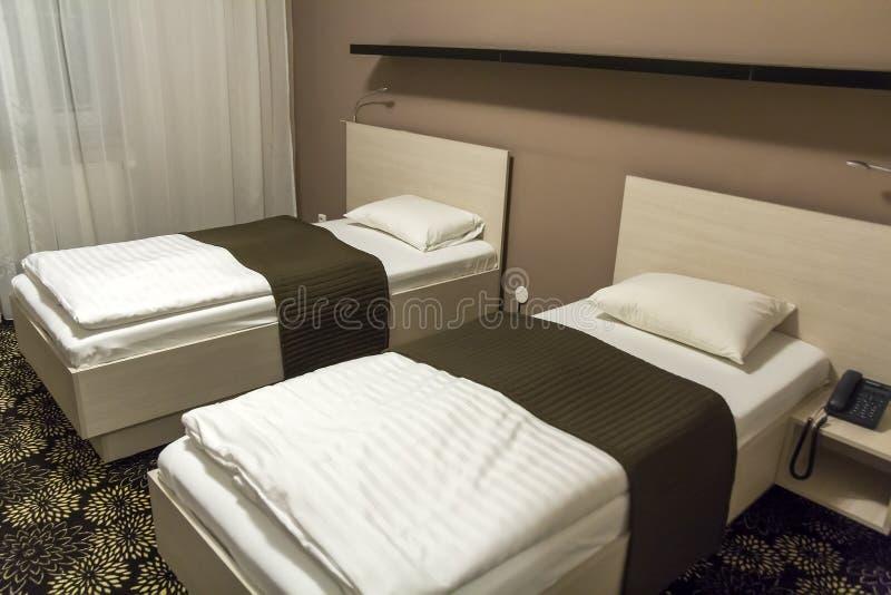 Hotelzimmerinnenraum mit zwei bequemen Betten stockbilder