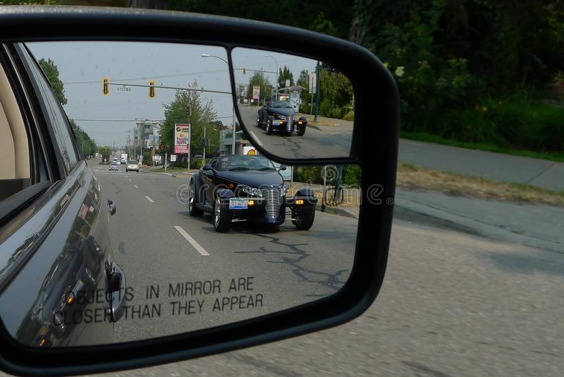 Hotrod Double Image in Car Mirror. Amazing double image of a rare Plymouth Prowler exotic sports car captured in the passenger mirror of a moving car stock photo