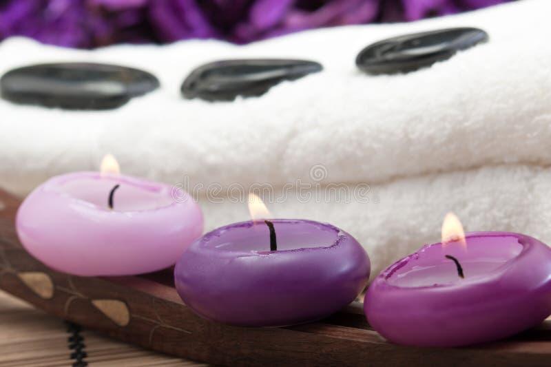 Hotstones auf Tuch mit Purpurkerzen (2) stockfotografie