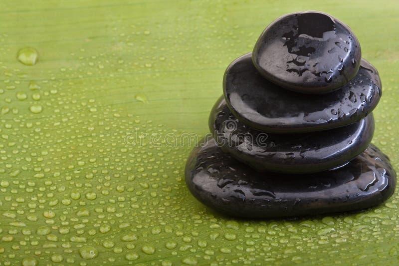 Hotstones molhados na folha verde da banana fotografia de stock