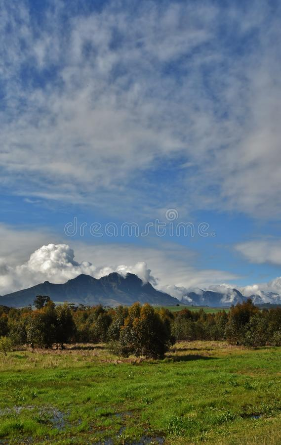 Hottentots Holland Mountains. Landscape with the Hottentots Holland Mountains and withe clouds in the sky stock image