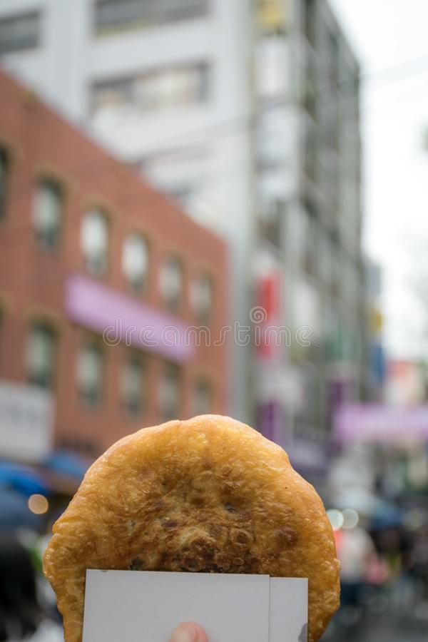 Hotteok or sweet Korean pancake with town in background. stock photo