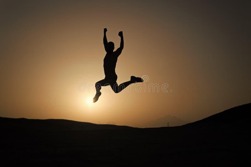 Houd bewegend De motiesprong van de silhouetmens voor de achtergrond van de zonsonderganghemel Dagelijkse motivatie Gezonde perso royalty-vrije stock afbeeldingen