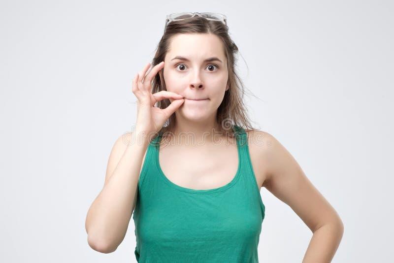 Houd een geheim, vrouw die haar gesloten mond snellen stock afbeelding