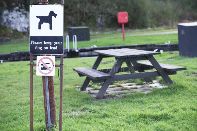 Houd hond op lood bij het teken van het de picknickgebied van het familiespel royalty-vrije stock afbeeldingen